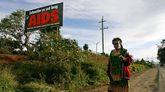 Una mujer camina descalza sobre el asfalto en Papúa Nueva Guinea; en el fondo, un cartel que alerta de la amenaza del virus del SIDA.