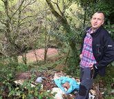 La basura cae por el talud al río Mendo en Trasanquelos.