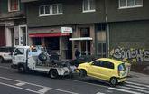 Una grúa municipal llevándose un coche ayer al depósito por la ronda de Outeiro.