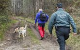 El perro, su guía y agentes de la Guardia Civil, en uno de los caminos por los que se concentró el rastreo.