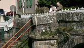 Varios vecinos observan la zona dañada del puente medieval.