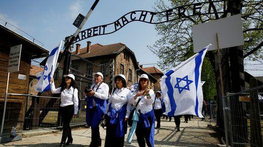 Gente ondea banderas israelíes en el campo de concentración de Auschwitz