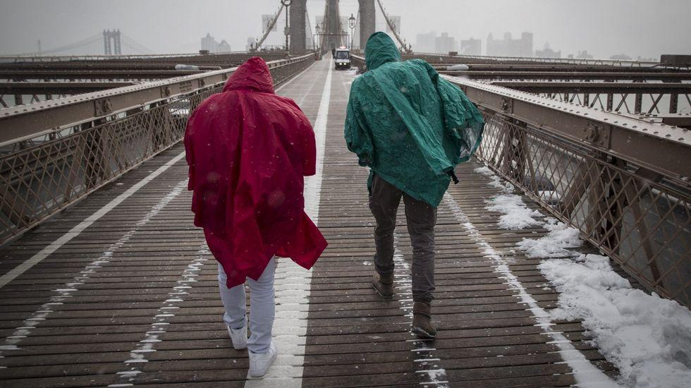 Dos turistas atravesando el puente de Brooklyn, en Nueva York.