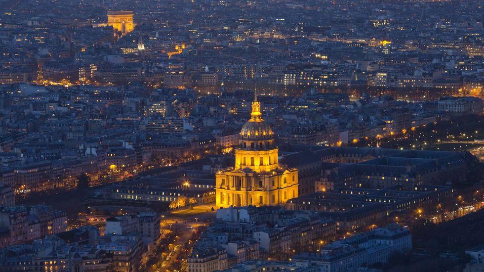 Vista aérea nocturna de les Invalides y, al fondo, el Arco del Triunfo en la capital francesa