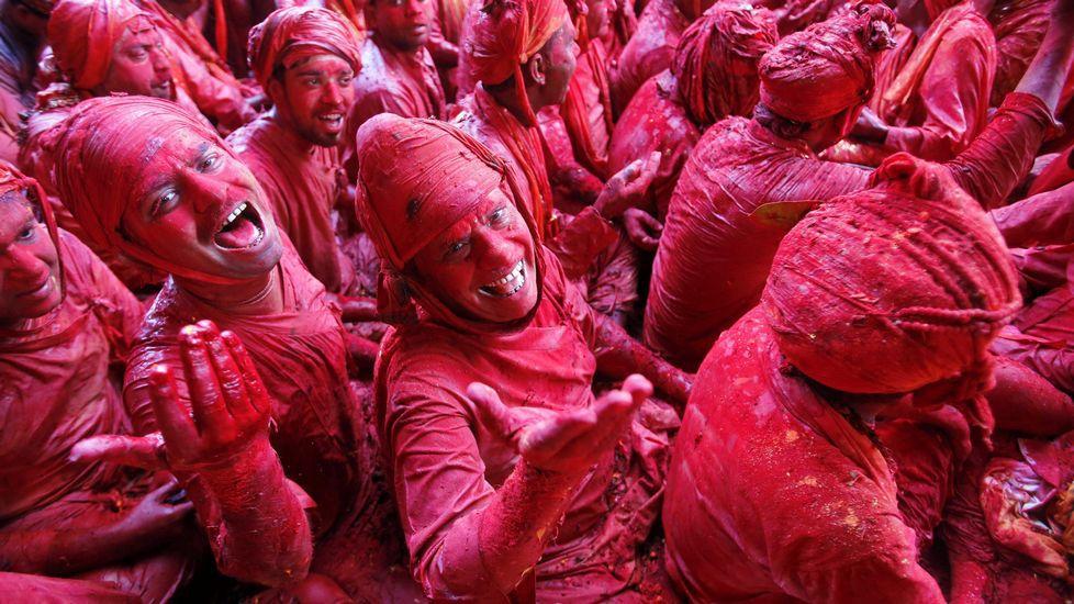 Varias personas cubiertas de polvo rojo participan en la celebración del festival hindú de Holi, en el templo de Radha Ran, en Mathura, para dar la bienvenida a la primavera.