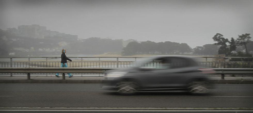 Un automóvil y una peatona transitan por el puente del Pasaje durante un día de niebla.
