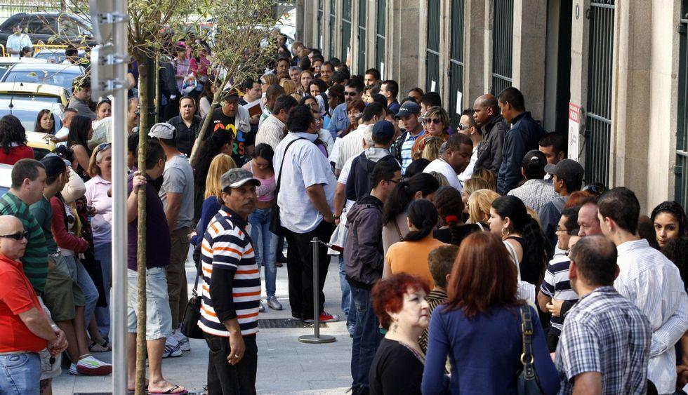 Cola de inmigrantes colombianos ante el edificio del Rectorado para solventar trámites legales.