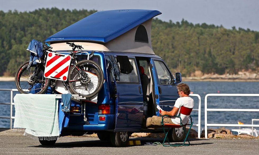 Un usuario con furgoneta adaptada relajado ayer en el puerto de Camariñas.