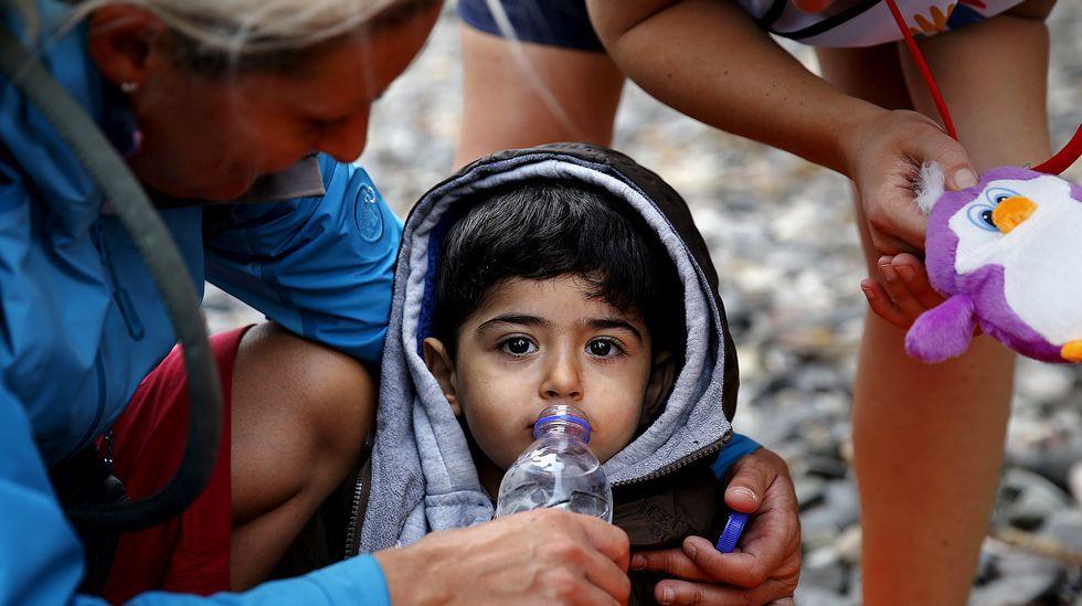 Una voluntaria ofrece agua a un niño sirio exhausto recién desembarcado en Lesbos.