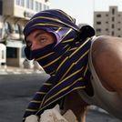 Dos palestinos enmascarados se cubren tras lanzar piedras contra los soldados israel�es.