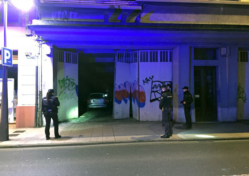 Agentes de la Policía Nacional comprobando el portal destartalado y el coche en el interior del garaje.