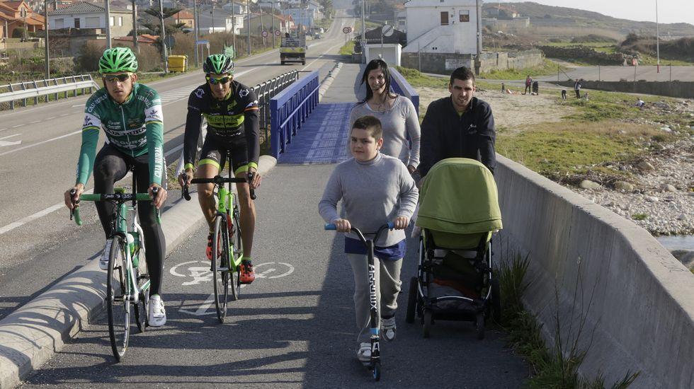 Bebés en la ruta. Una familia con un carrito de bebé y un niño con patinete pasean por el carril bici a la altura de Mougás. Los peatones deberían usar el arcén, pero en ese tramo no existe en el lado contrario. Ellos mismos lo dicen y comprenden que son un obstáculo para los ciclistas. Hay comprensión por ambas partes.